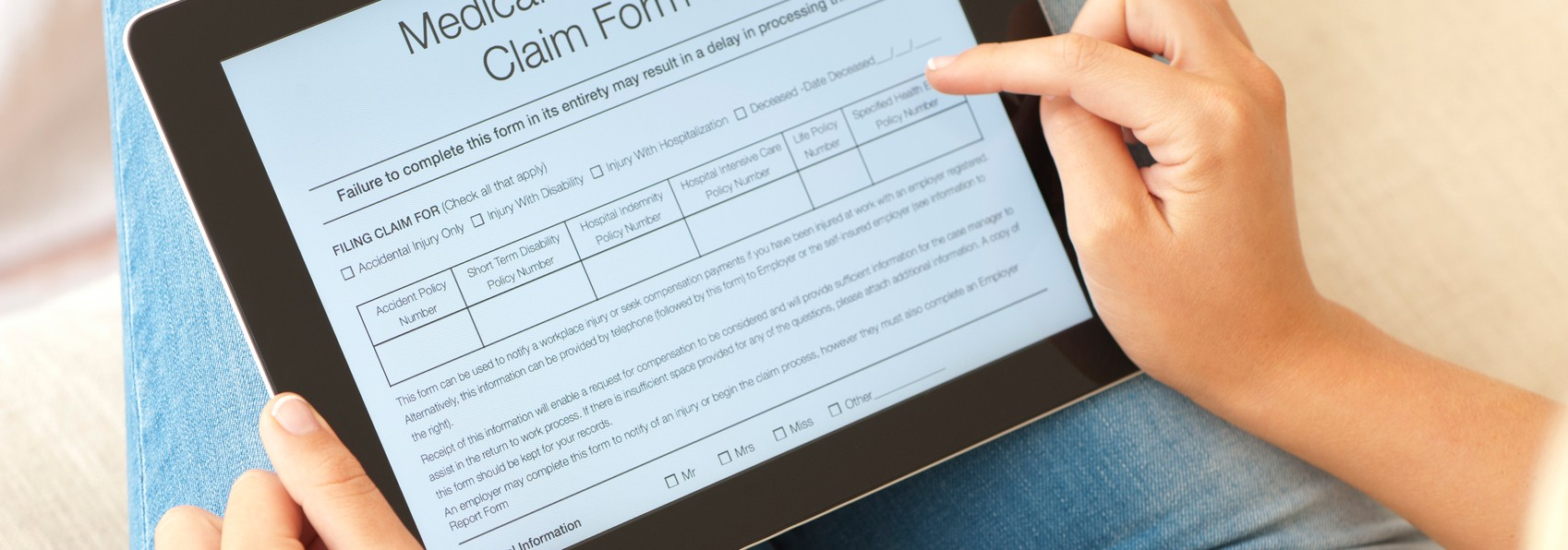 a woman reading medical claim form on table device